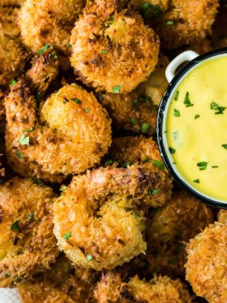 A close up of a plate of crispy coconut shrimp with mango dipping sauce on the side.