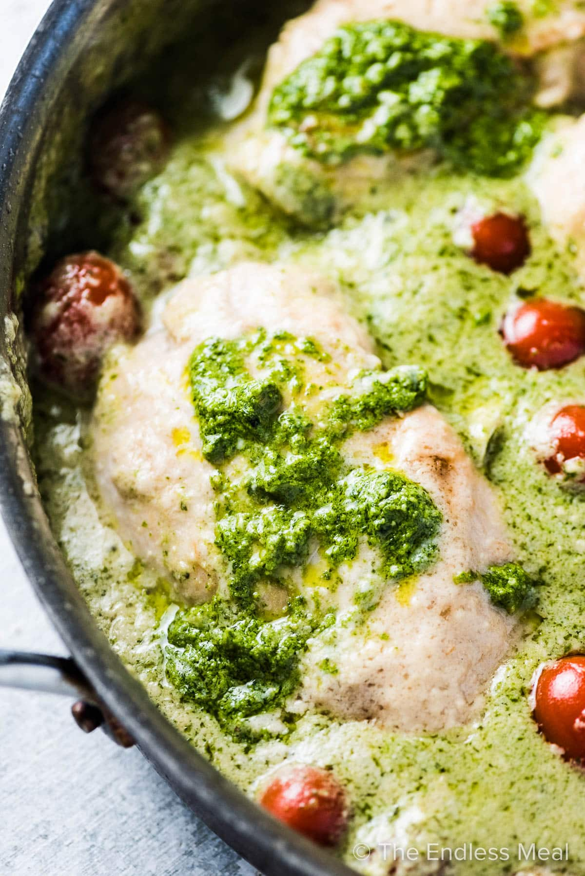 A close up of creamy pesto chicken in a pan with some cherry tomatoes.