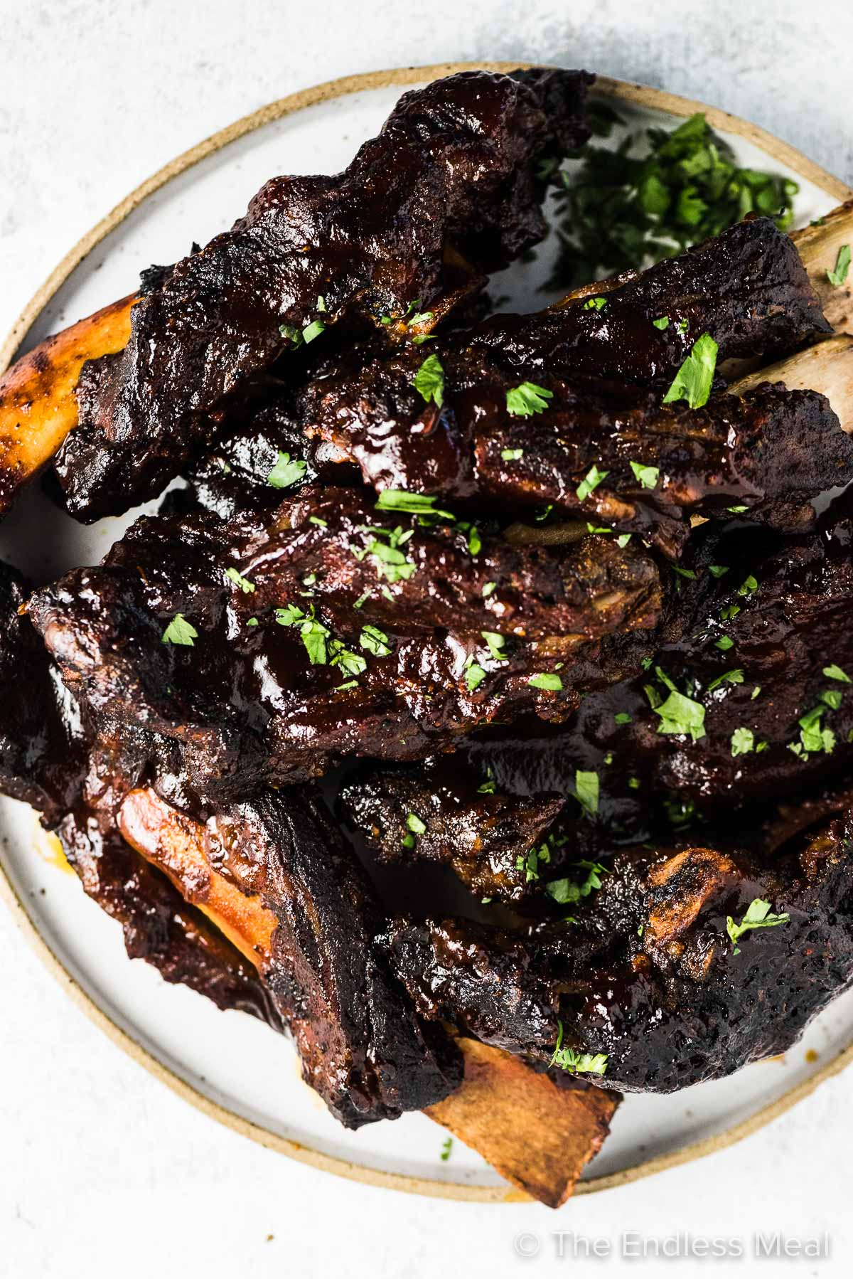 A big pile of sticky crockpot beef ribs on a serving plate.