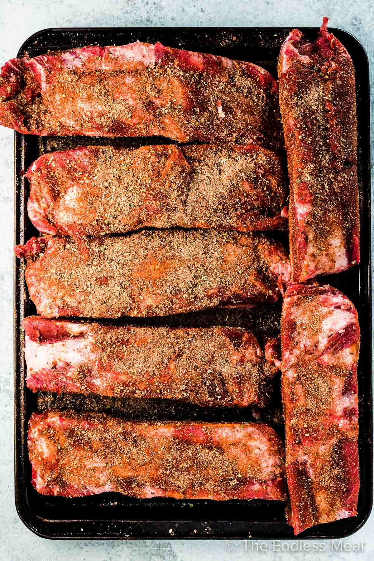 Uncooked beef back ribs with spices on them on a baking tray.