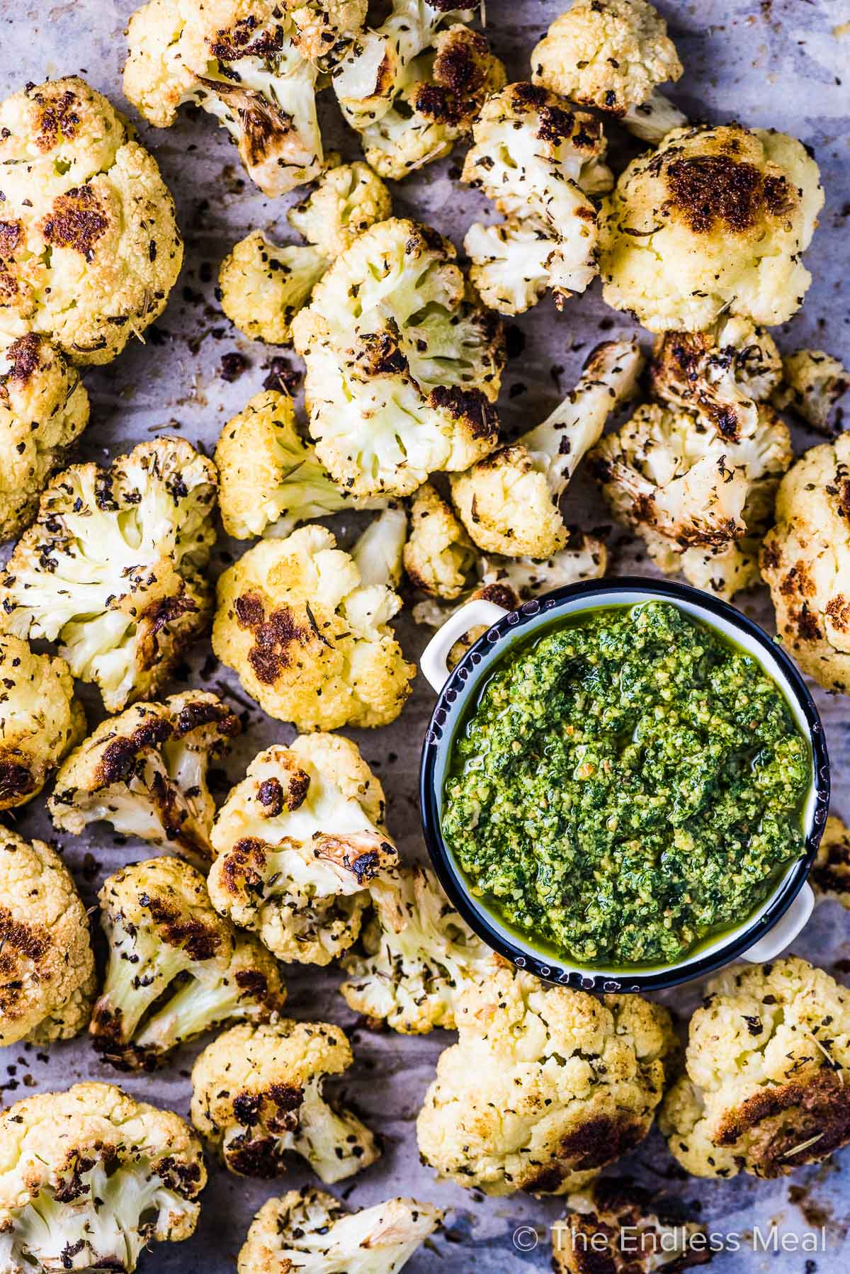 Roasted Italian cauliflower on a baking sheet with a bowl of pesto,