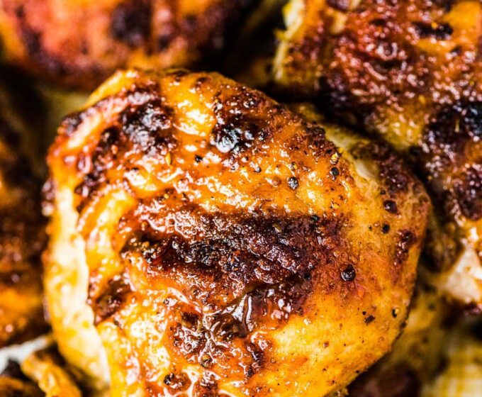 A close up of a stack of juicy baked chicken thighs.