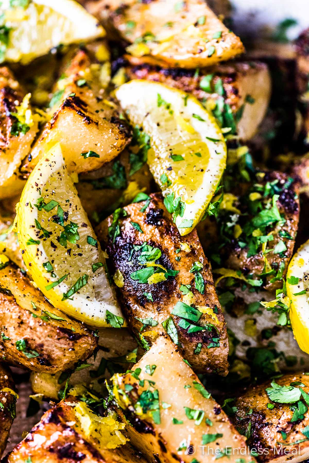 A close up of Greek lemon potatoes with a few slices of lemon on top.