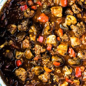 A big pot of sausage chili with lots of sausage chunks and mushrooms in it.