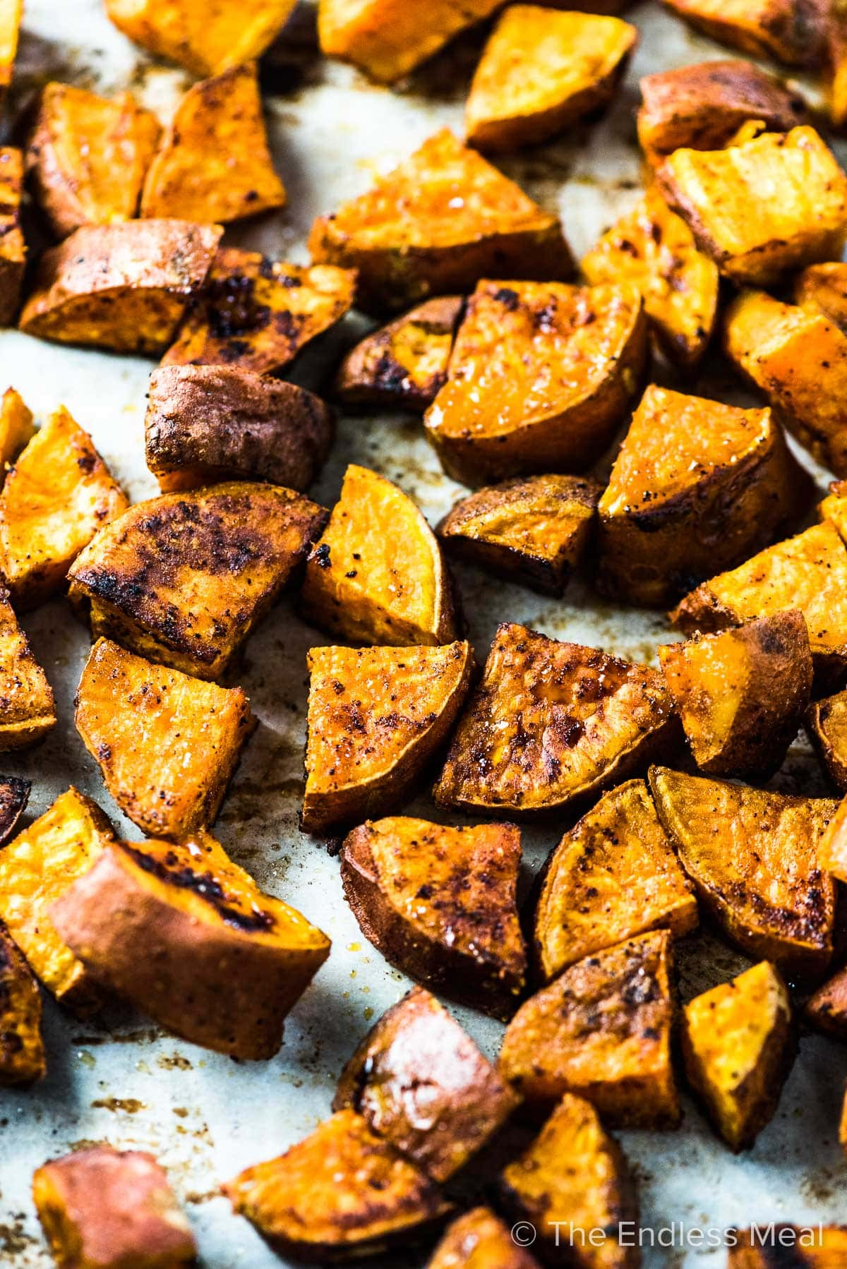 Spiced roasted sweet potatoes on a baking sheet.