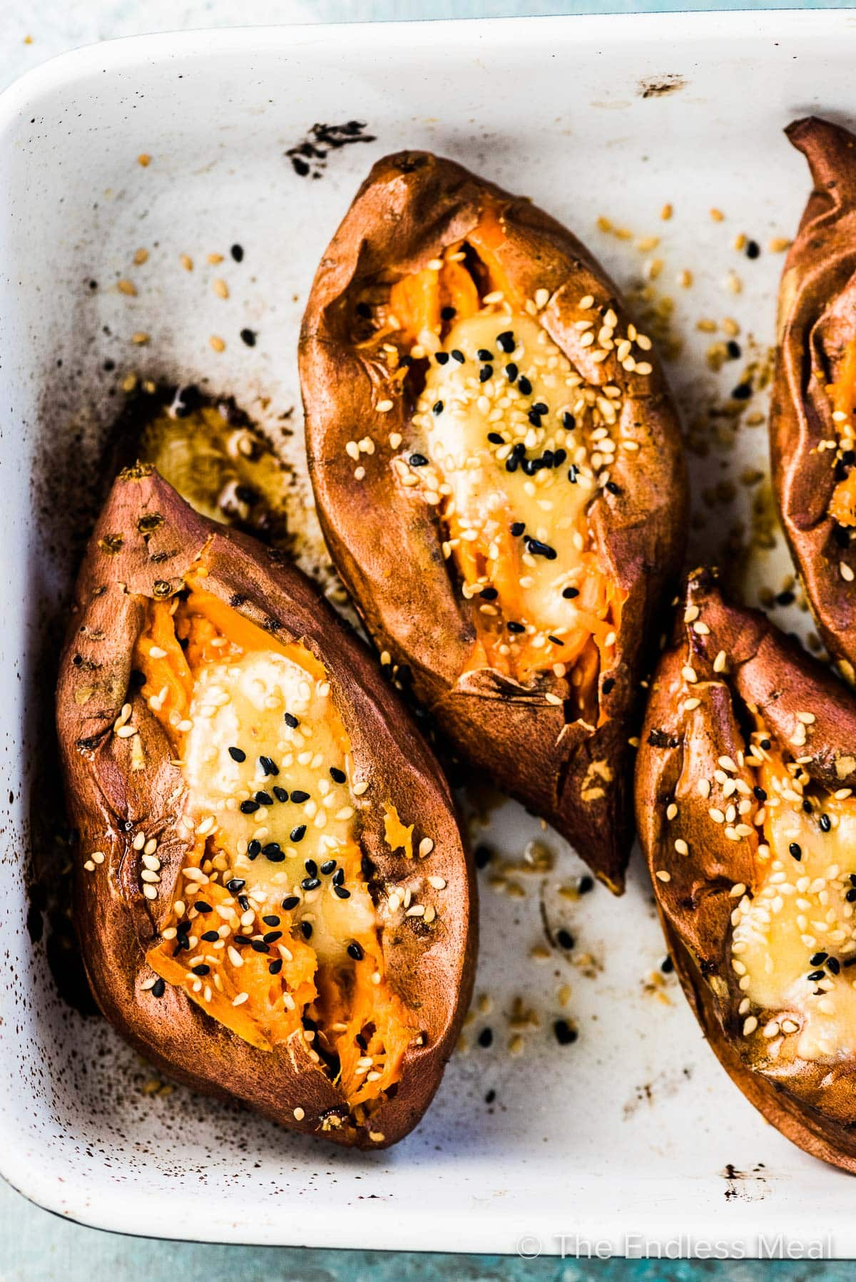 Cut open roasted sweet potatoes in a baking dish with melting miso tahini butter over the top.