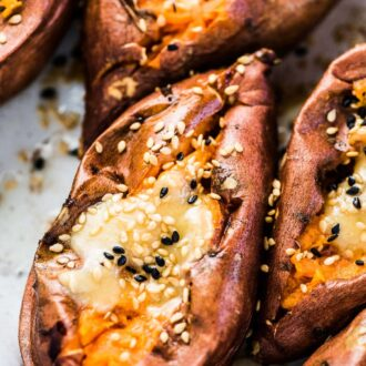 A close up of a baked sweet potato cut open with miso tahini butter on top and a sprinkle of sesame seeds.