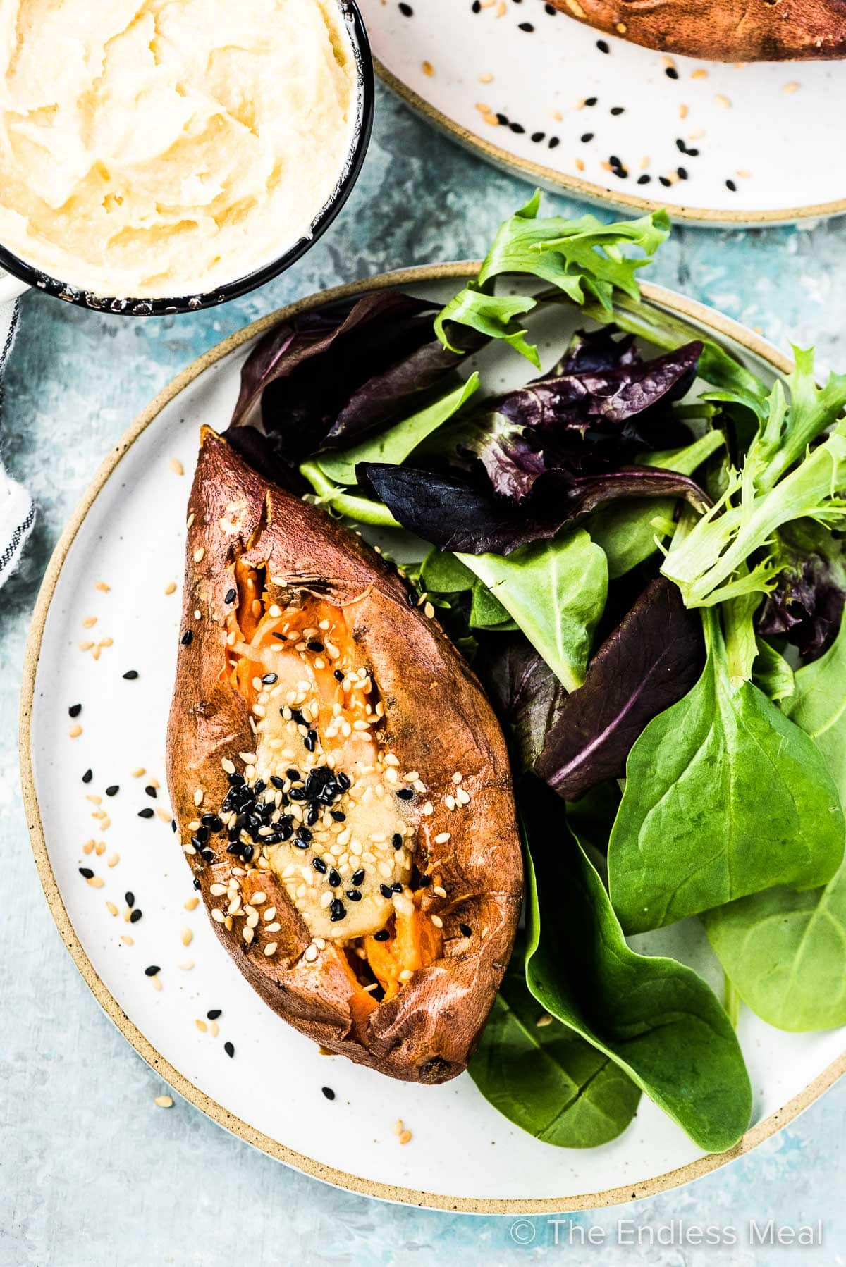 A roasted sweet potato on a plate with some salad and miso tahini butter melting on top.