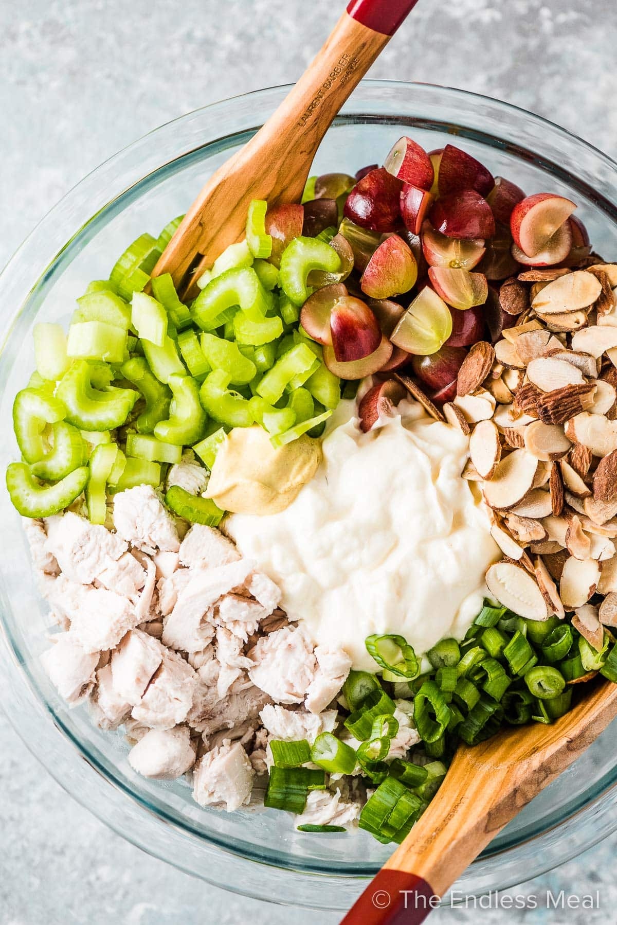 All the ingredients for how to make chicken salad in a glass bowl.