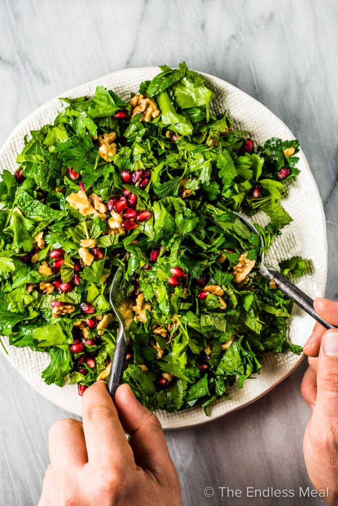Hands dishing out some of this Christmas salad recipe.