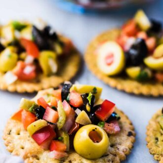 Olive salsa piled on top of crackers.