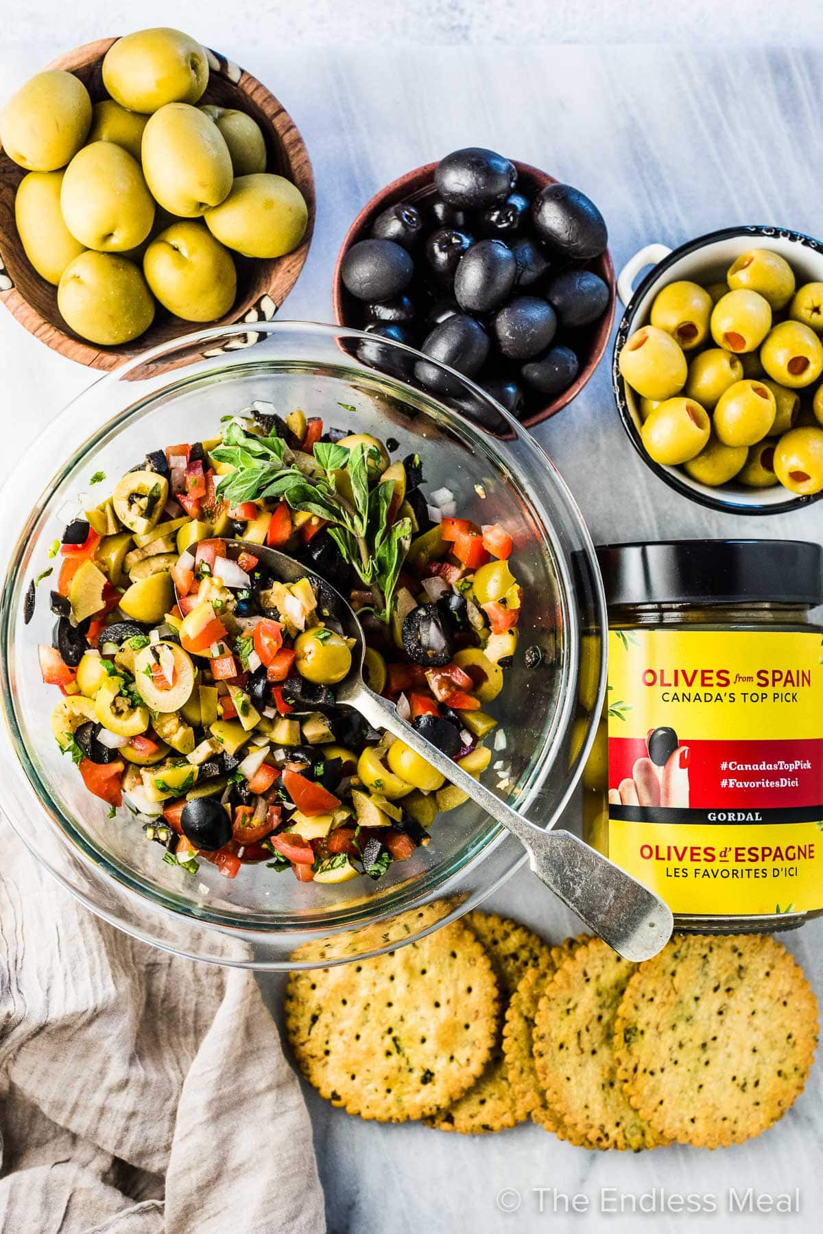 A glass bowl filled with olive salsa and bowls of olives surrounding it.