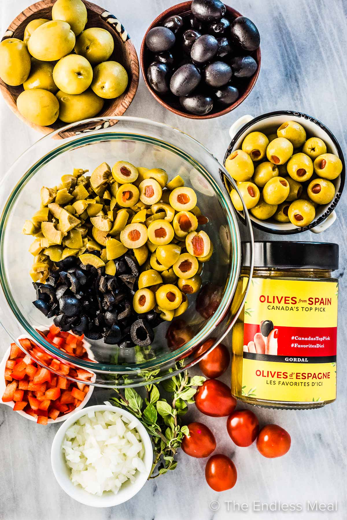 All the ingredients for this olive salsa recipe laid out on a marble counter.