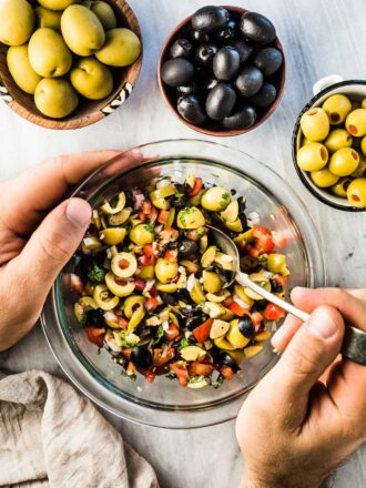 Hands mixing a bowl of olive salsa.