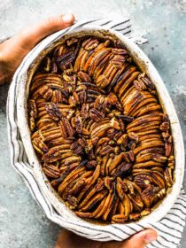 Hands holding this pretty sweet potato casserole.