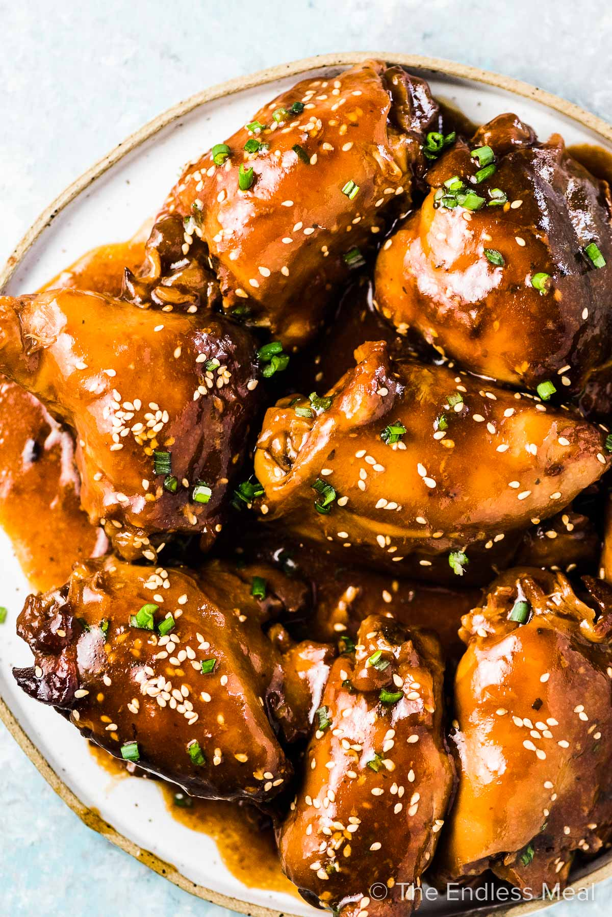 Slow cooker honey garlic chicken thighs on a white plate.