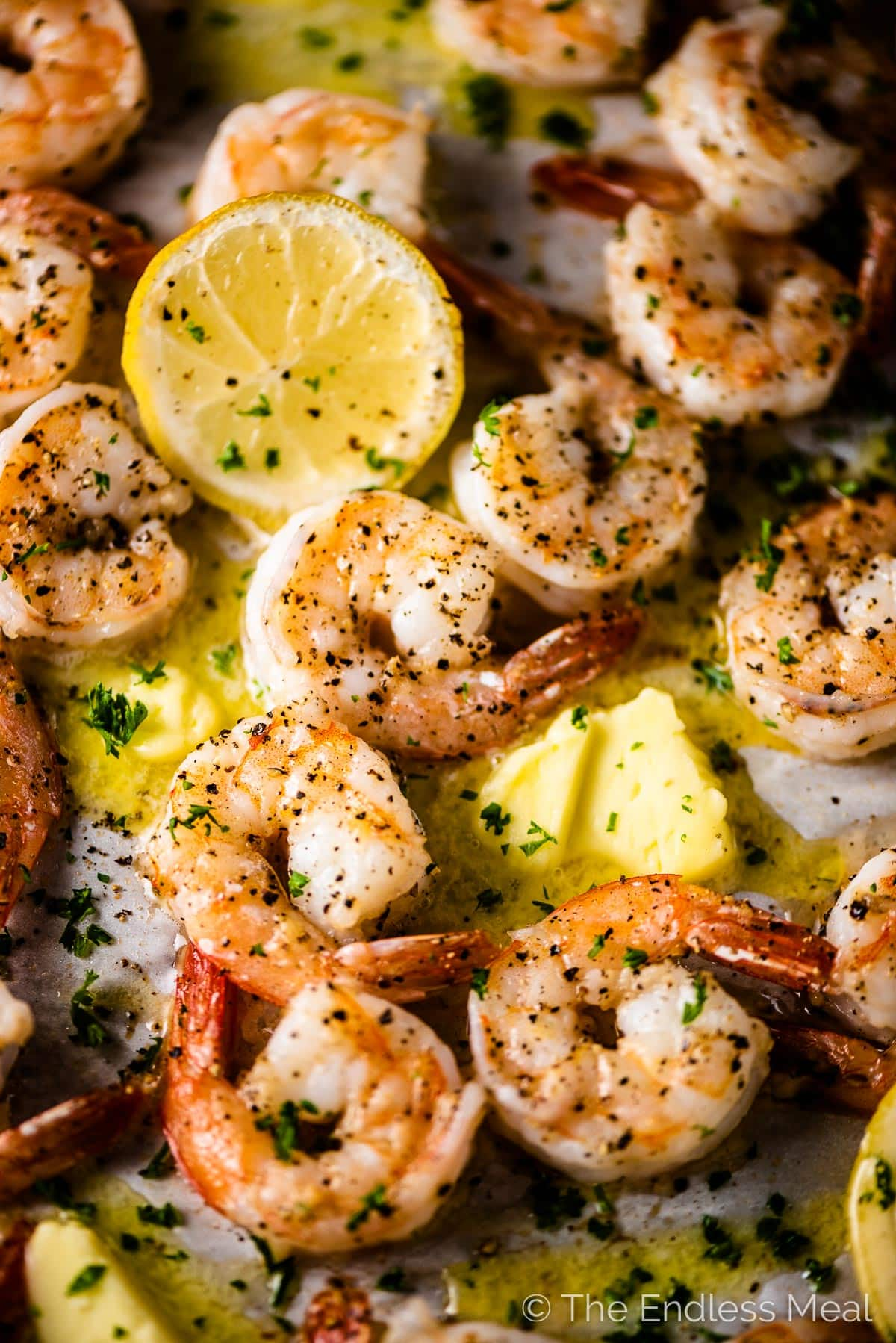 Garlic butter baked shrimp on a tray with slices of lemon and pats of butter.