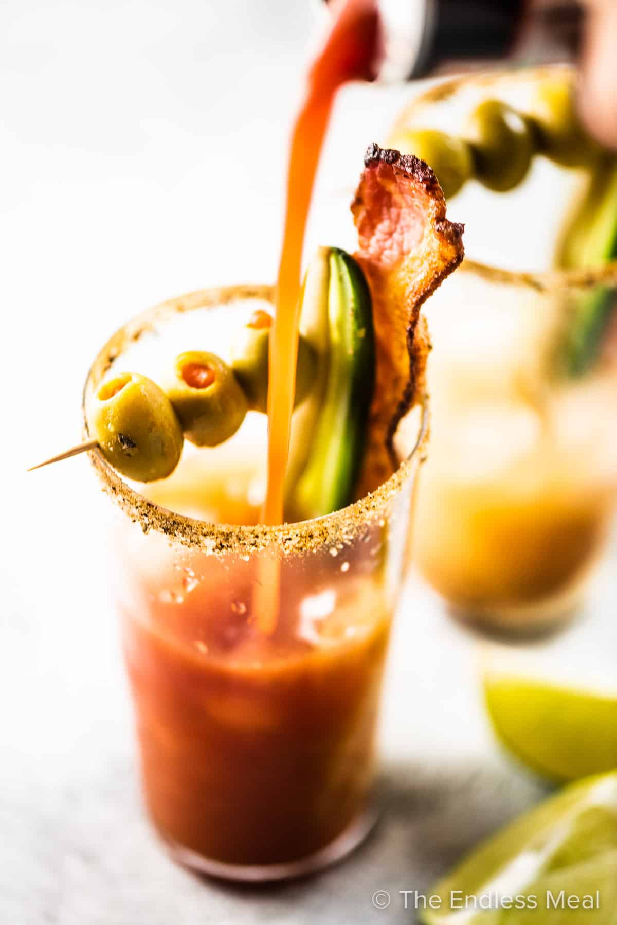 Bloody Caesar being poured into a tall glass cup.