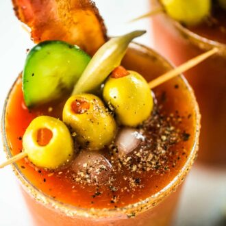 A close up of the best Bloody Caesar drink with olives, bacon, pickled bean, and cucumber as garnish.