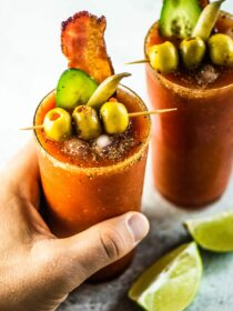 A hand grabbing a Caesar cocktail made with homemade Clamato.