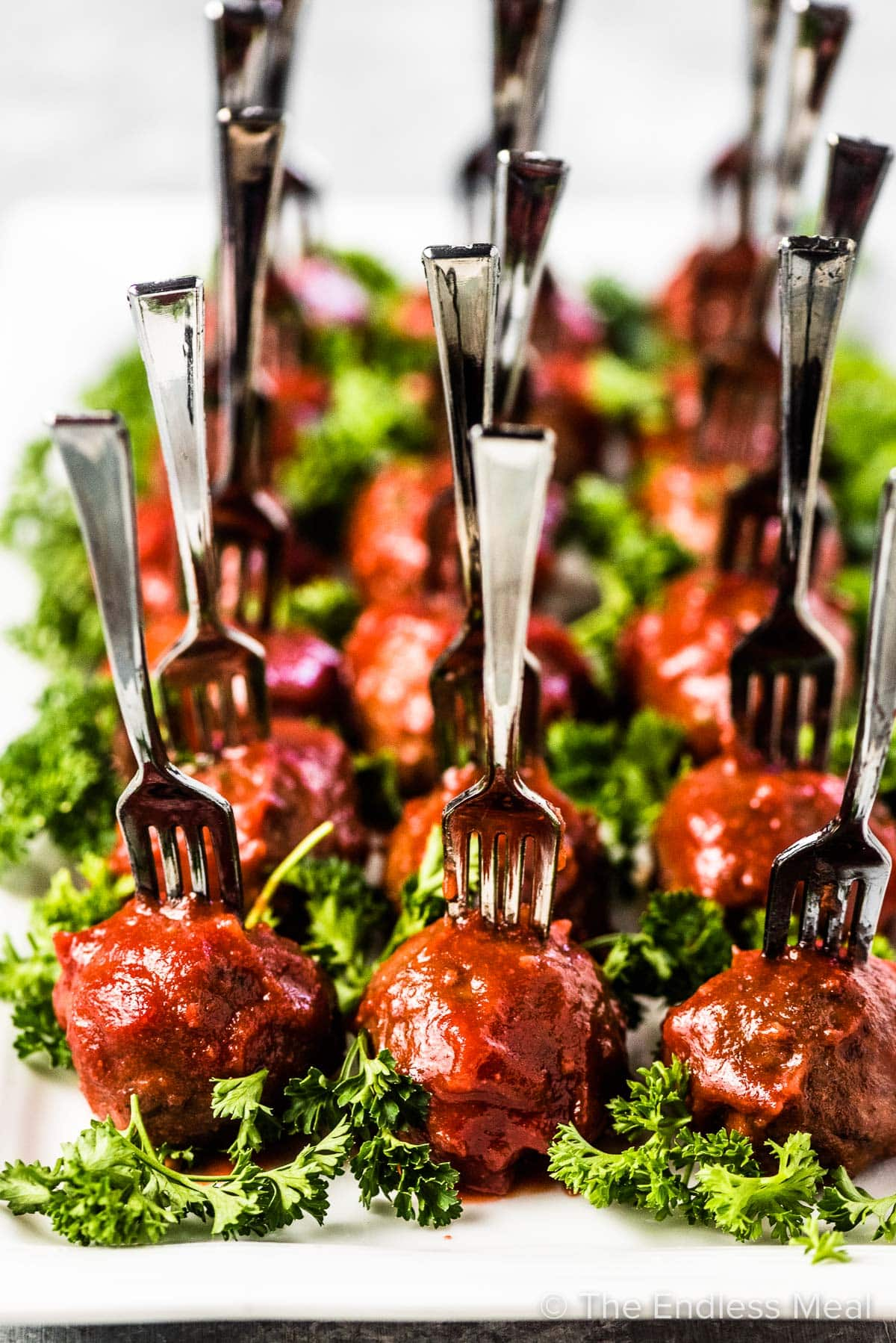 Cranberry meatballs on a serving tray with little forks in them and some greens sprinkled around.