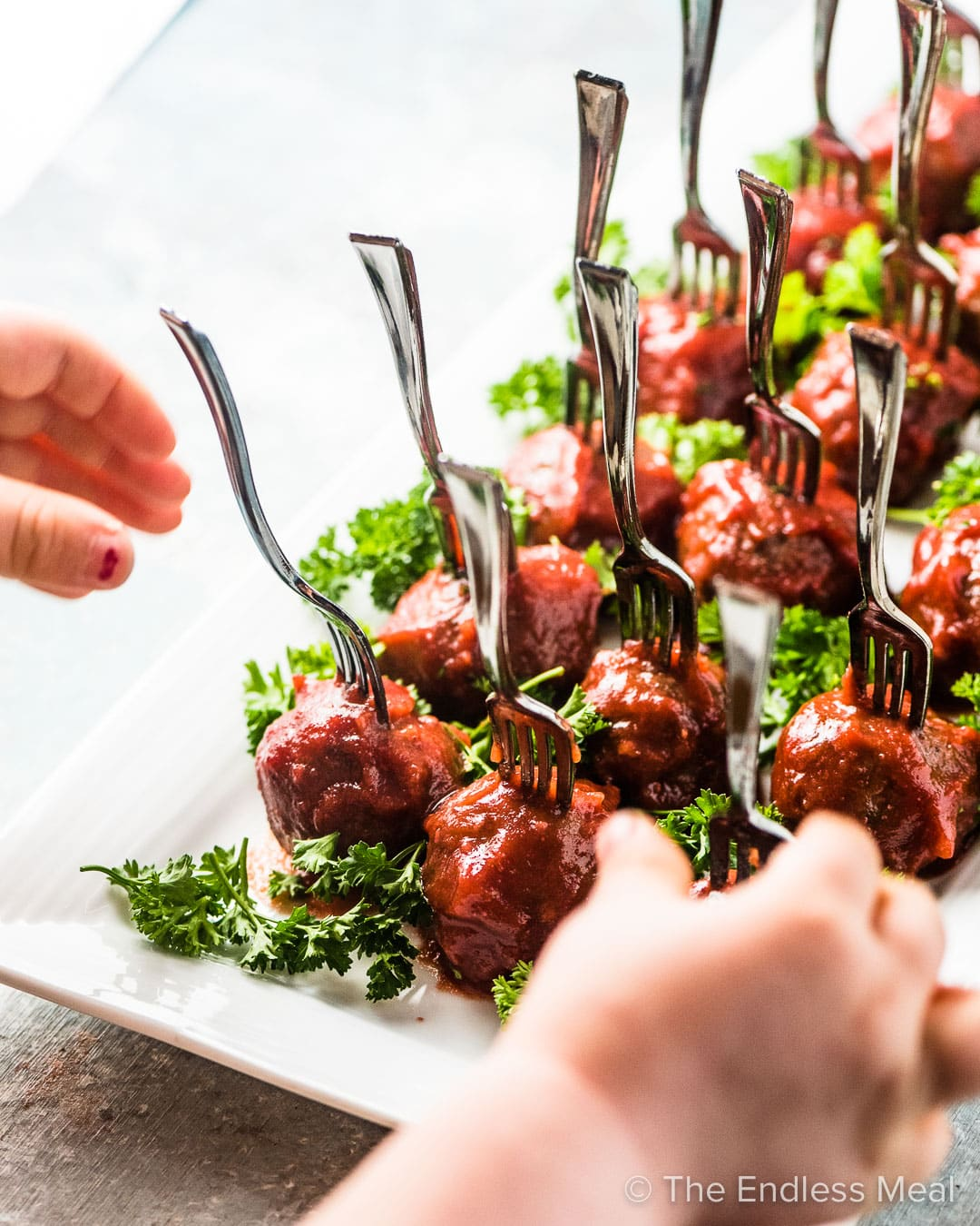 Hands reaching for these cranberry meatballs on a white plate.