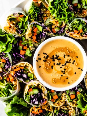 Fresh spring rolls on a plate with a bowl of tahini dipping sauce.