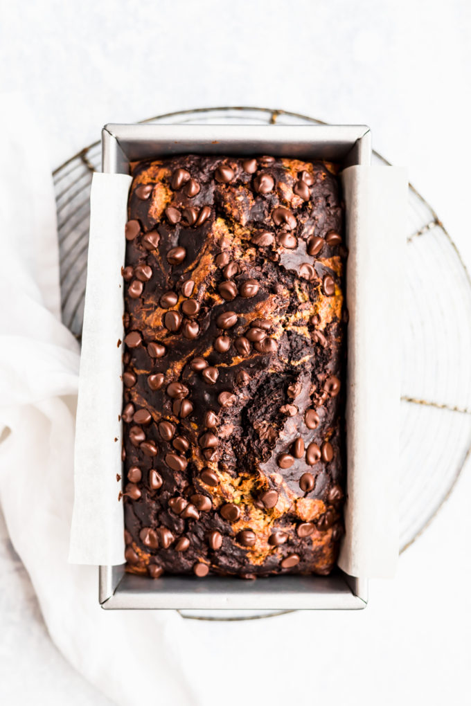 A bread pan on a cooling rack full of marbled chocolate zucchini banana bread with chocolate chips on top