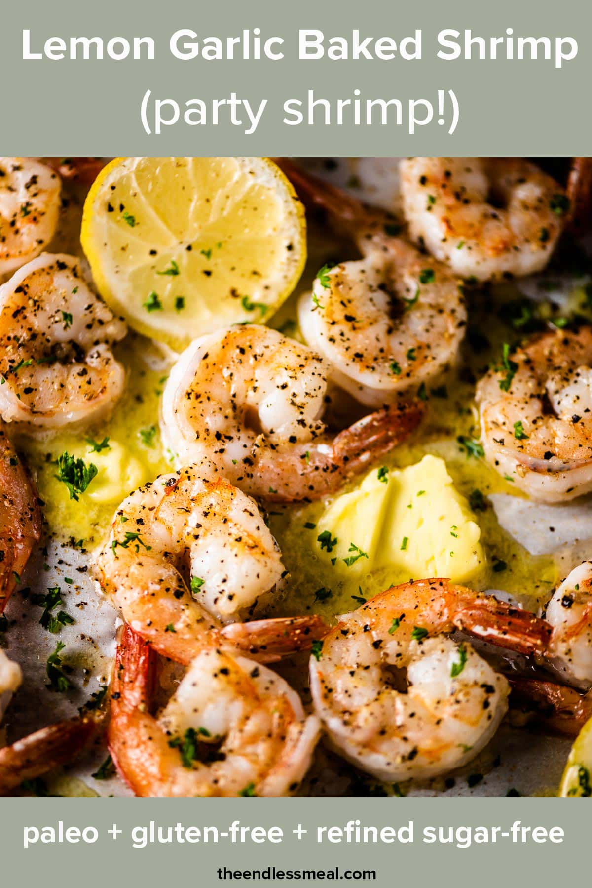 Lemon garlic butter baked shrimp on a tray with lemons and the recipe title on top of the picture.