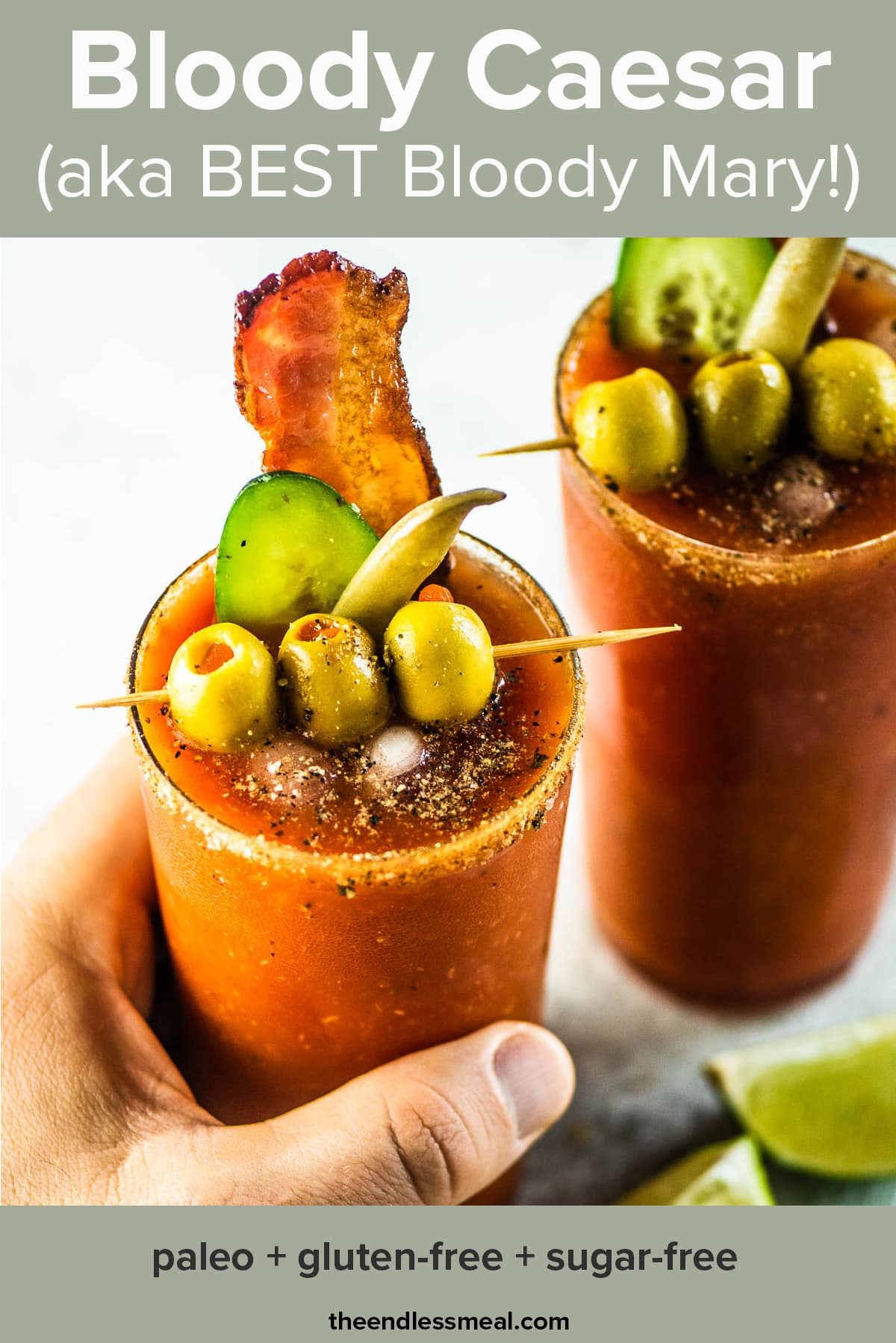 A hand grabbing a Caesar cocktail made with homemade Clamato with the recipe title on top of the picture.