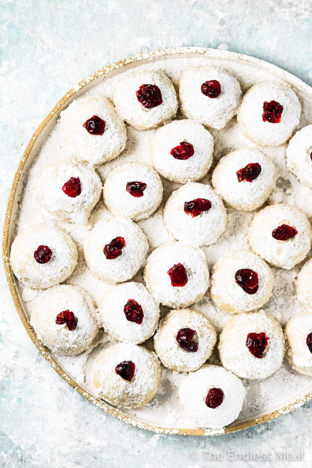A plate filled with snowball keto Christmas cookies topped with cranberries.