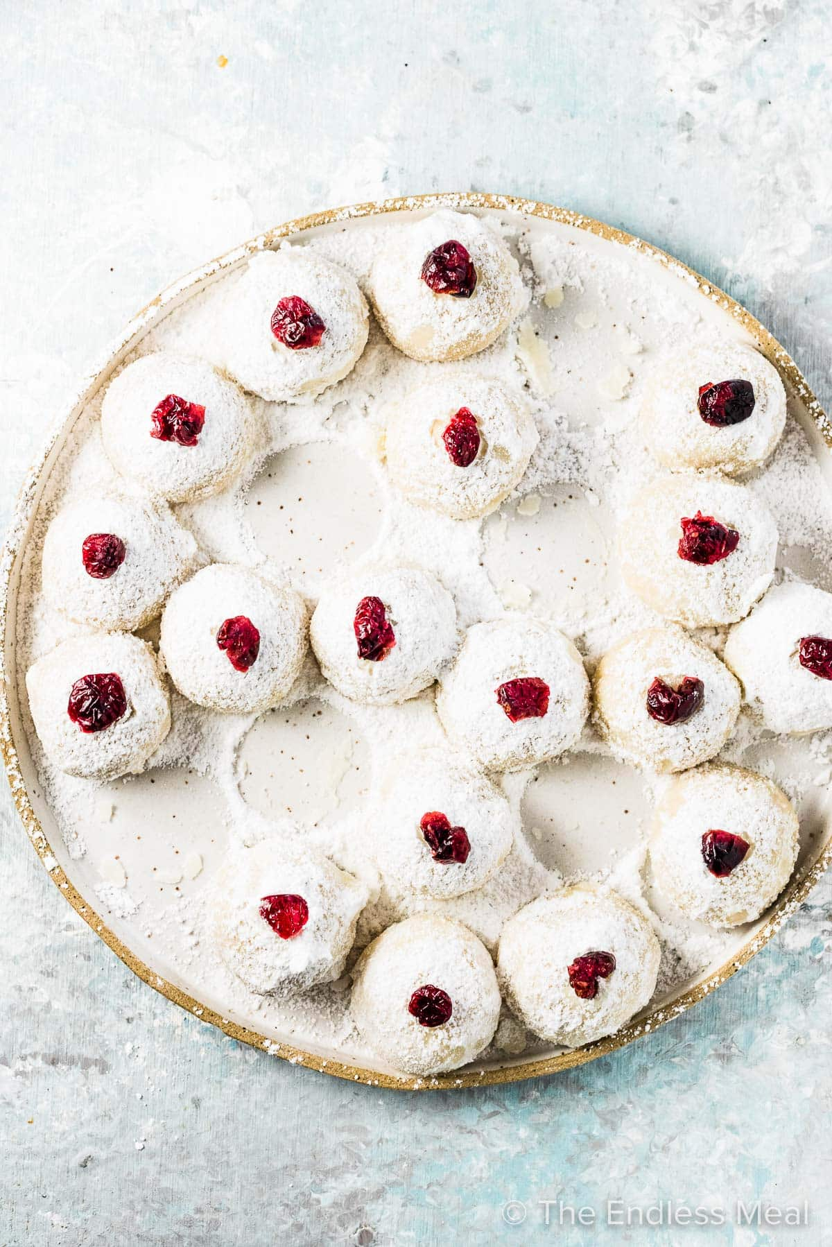 A plate of almond flour shortbread cookies topped with cranberries with a few missing from the plate.