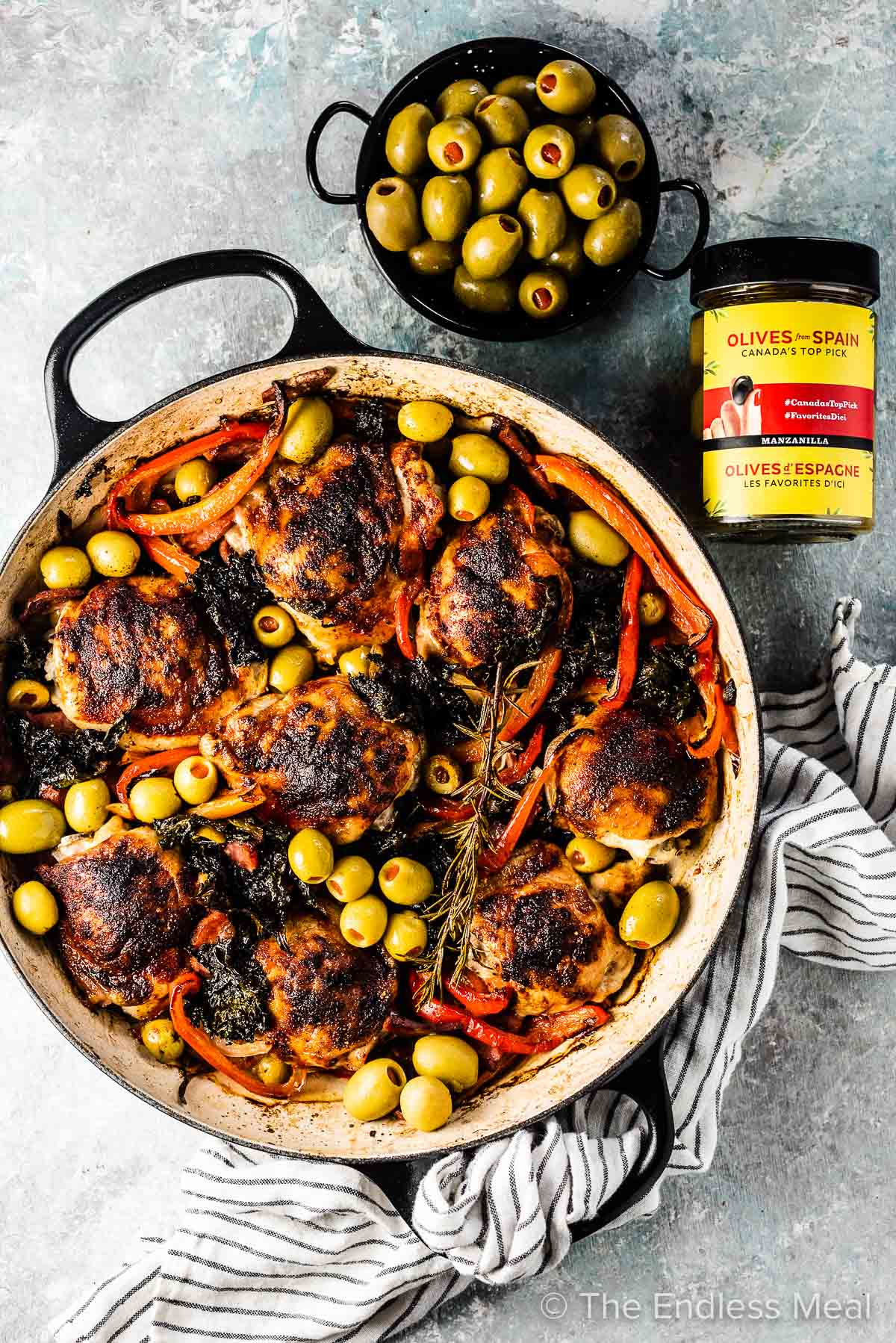 A big skillet of this Spanish chicken bake and a jar and bowl of Spanish manzanilla olives on the side.