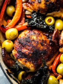 A close up of a this Spanish chicken bake with olives, kale, peppers, and chorizo.