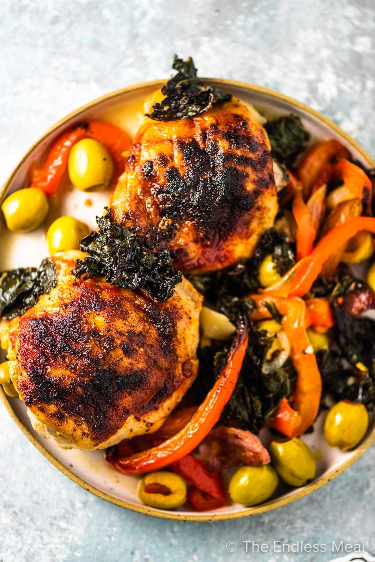 2 baked Spanish chicken thighs on a plate with peppers, crispy kale, and lots of olives.