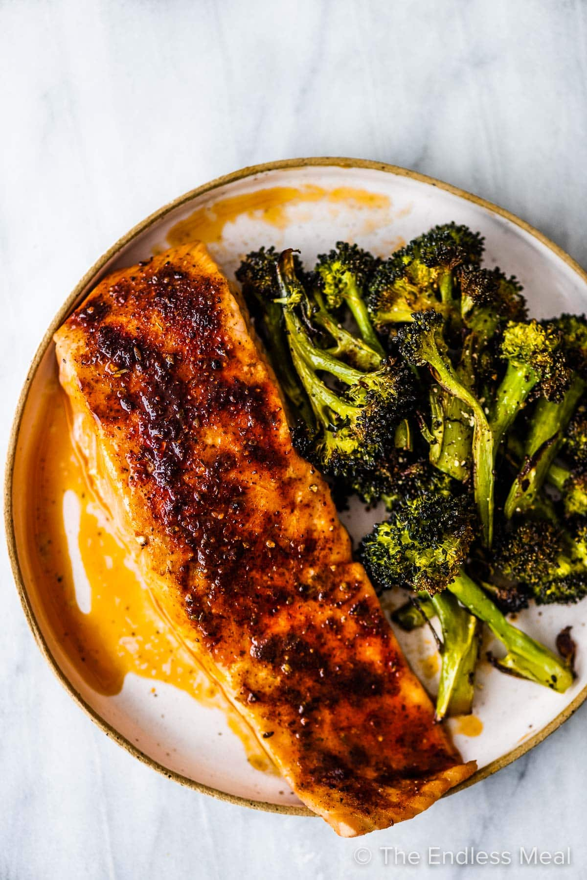 A piece of baked salmon on a plate with a side of broccoli.