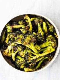 A serving bowl full of roasted broccoli