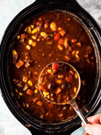 Looking down on vegetarian chili in a slow cooker with a ladle taking a scoop.