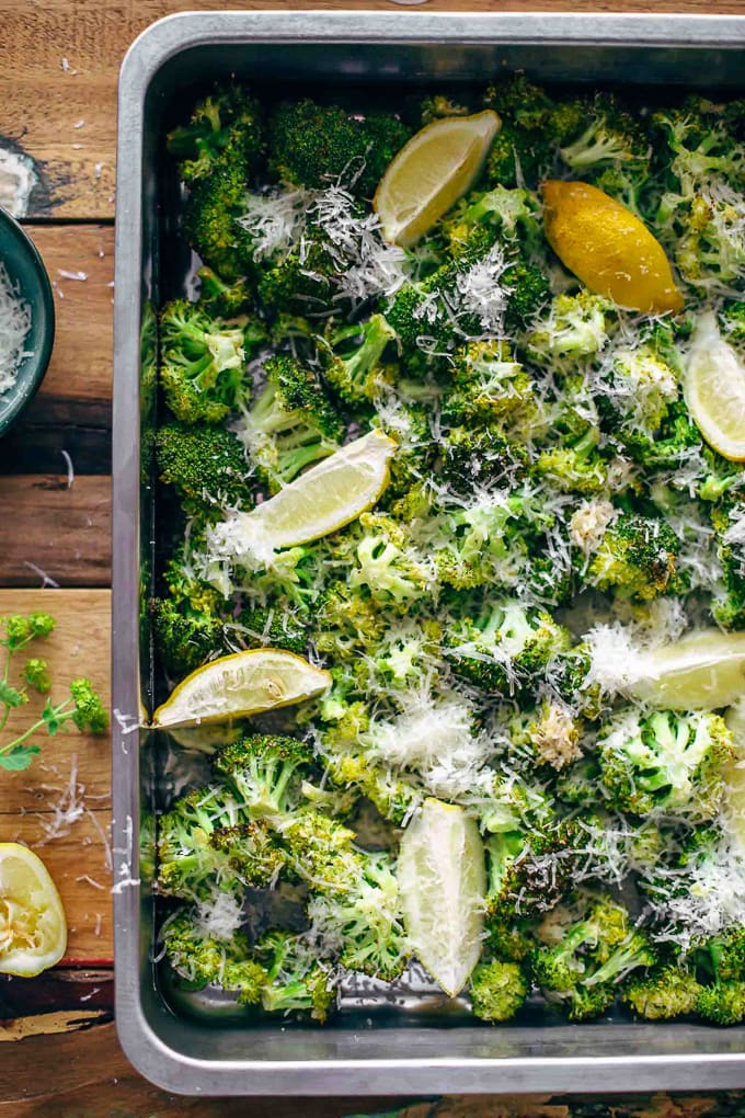 A sheetpan full of roasted broccoli, lemon wedges and parmesan cheese shreds