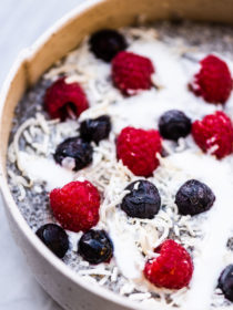 Chia seed pudding in a white bowl topped with blueberries and rasberries.