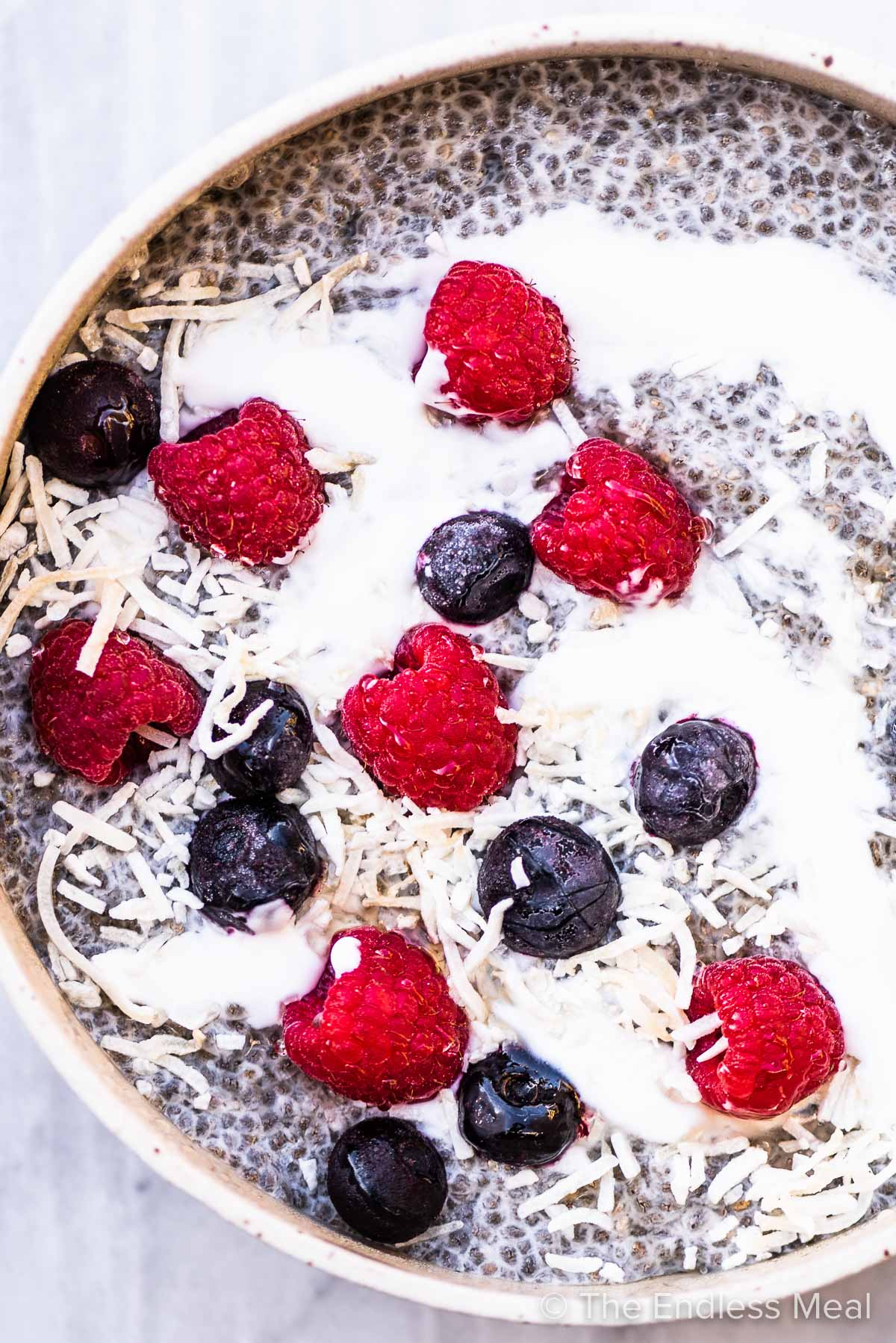 Chia seed pudding with coconut and berries in a bowl.