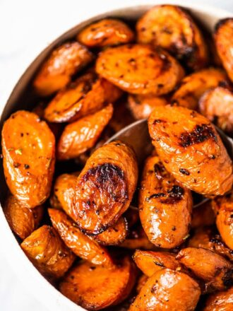 A white bowl filled with easy garlic roasted carrots.