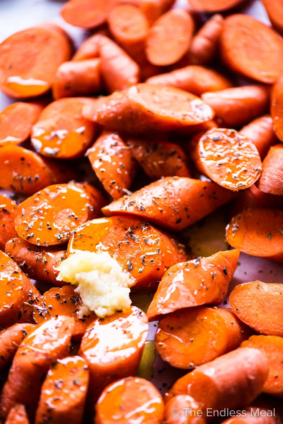 Sliced carrots on a baking sheet with spices and garlic.