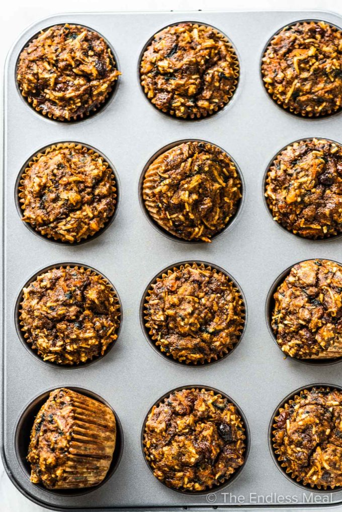 A muffin tray filled with healthy carrot cake muffins.