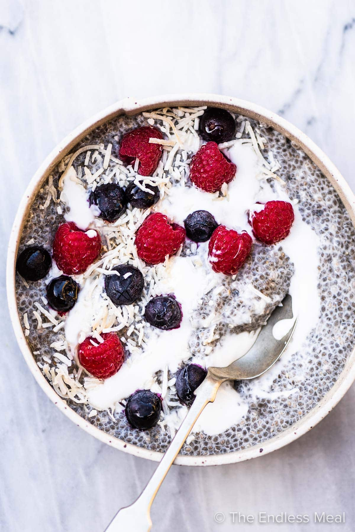 white bowl with chia seed pudding, topped with coconut, milk, and berries