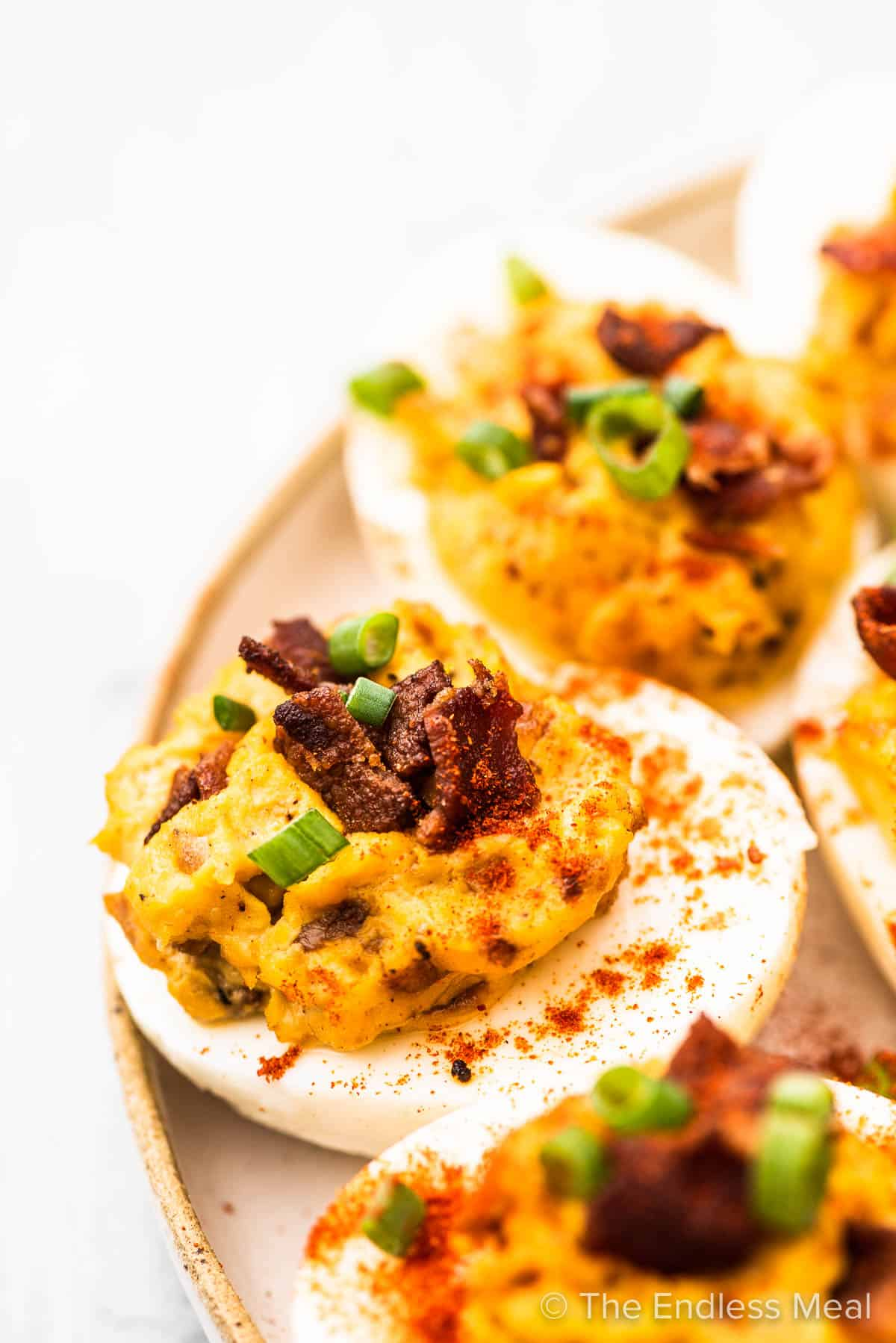 Deviled eggs with bacon and topped with green onions on a plate.