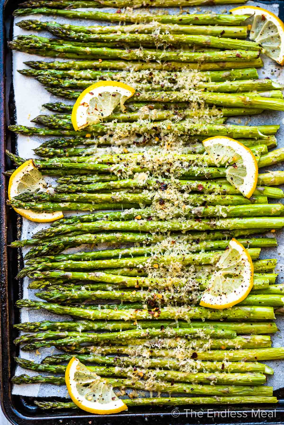 A baking sheet with roasted asparagus lined up on it.