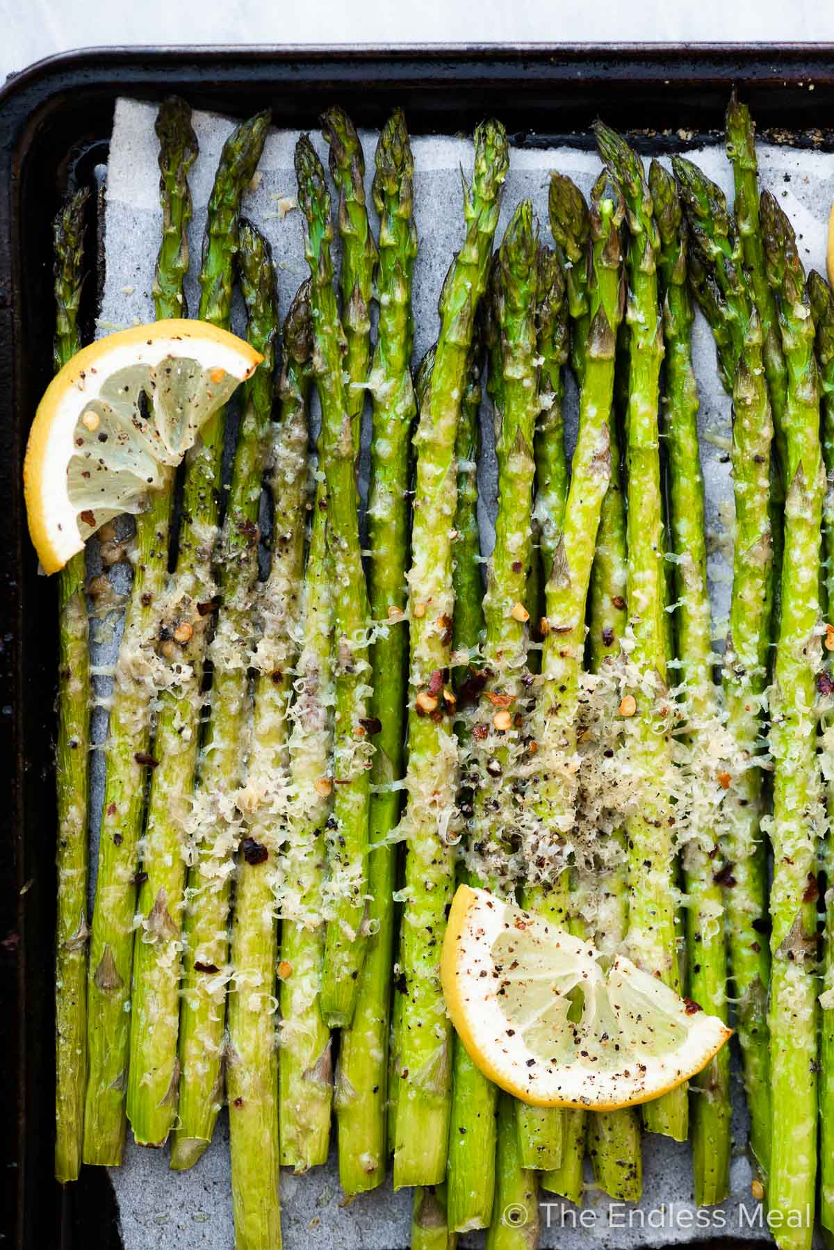 Roasted asparagus on a baking sheet with lemon and parmesan.