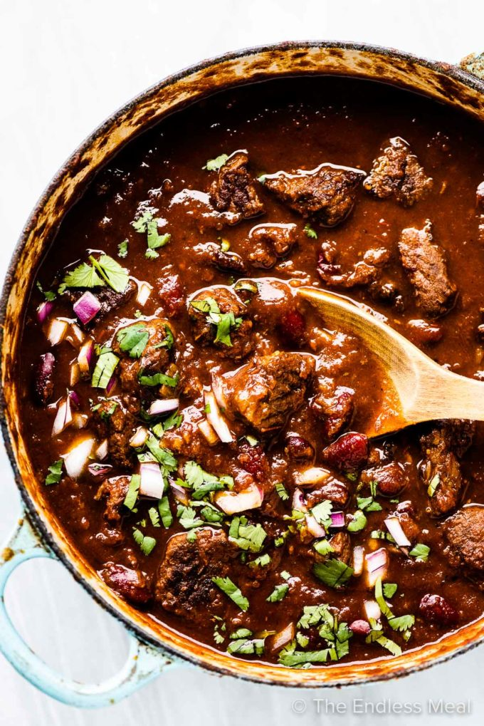 A spoon taking a scoop of the best steak chili out of a pot.