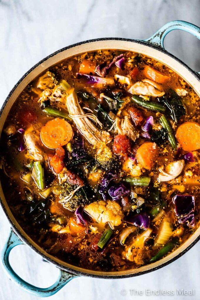 A blue cast iron pan filled with colorful vegetables and chicken soup